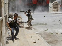 A Free Syrian Army fighter prepares to fire a RPG as a Syrian Army tank shell hits a building across a street during heavy fighting in the Salaheddine neighbourhood of central Aleppo