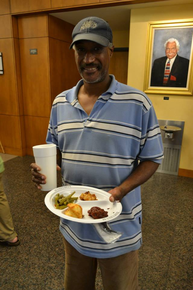 """Launch party attendee enjoys a plate of church supper food from the Rural South room of the """"Soul Food"""" book launch party"""