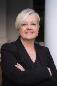 Pictured: Karen L. Cox, author photo; person wearing an all black suite and earrings who has short blonde hair and blue eyes.