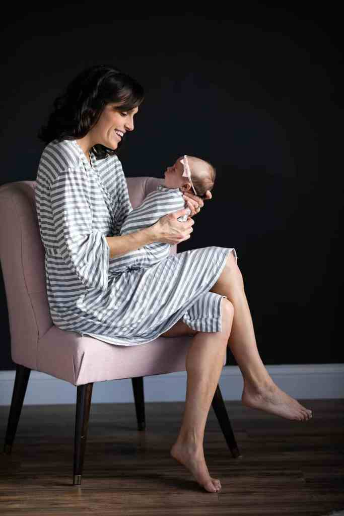 mom-in-gray-and-white-striped-postpartum-pajamas-holding-baby-in-matching-swaddle