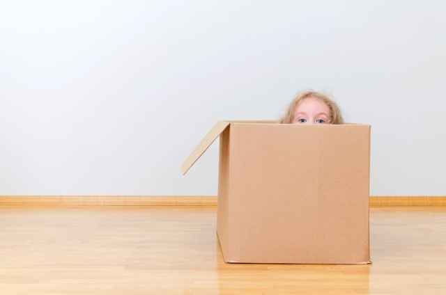 child hiding in moving box