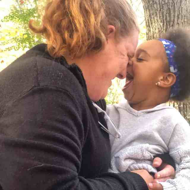 white mother and mixed race daughter holding their noses together while laughing