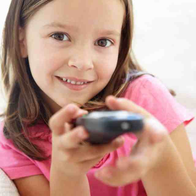 Little girl smiling while holding remote control for television