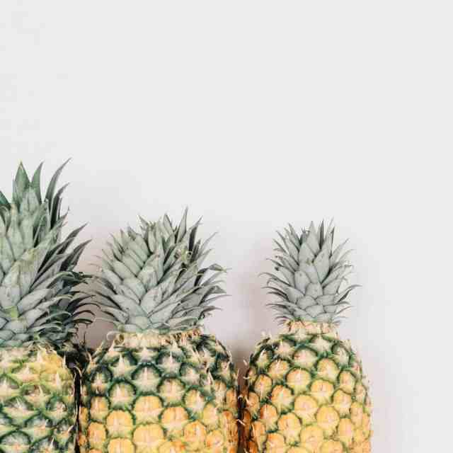 three pineapples laying side by side