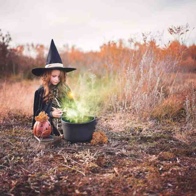 little girl dressed as a witch while playing with cauldron