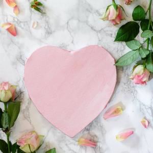 This photo shows a pink heart on top of a marble background, surrounded by pink roses.