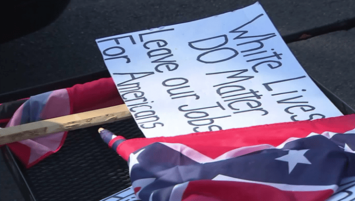"Signs read ""White lives do matter. Leave our jobs for Americans,"" (far right of image) ""Wake up White America. Your history is being hidden or erased,"" pictured with Confederate. Ku Klux Klan rally in Anaheim, Ca"