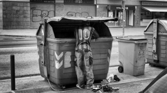 un-hombre-busca-comida-en-un-contenedor-de-basura-es-espac3b1a