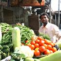 indian man standing behind vegetable stand