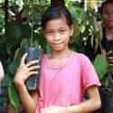 young girl holding radio in front of trees