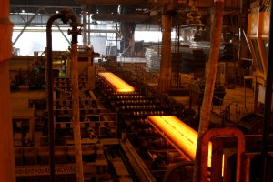 molten hot steel beams being transported over a conveyer belt