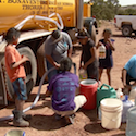 Navajo family gathers around water truck.