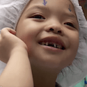 A young eye surgery patient smiles