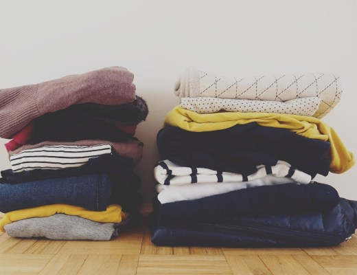 Two piles of decluttered clothes that will be donated or sold