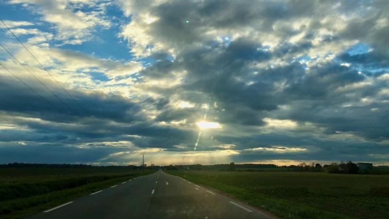 paysage de route vers l'horizon et soleil déclinant
