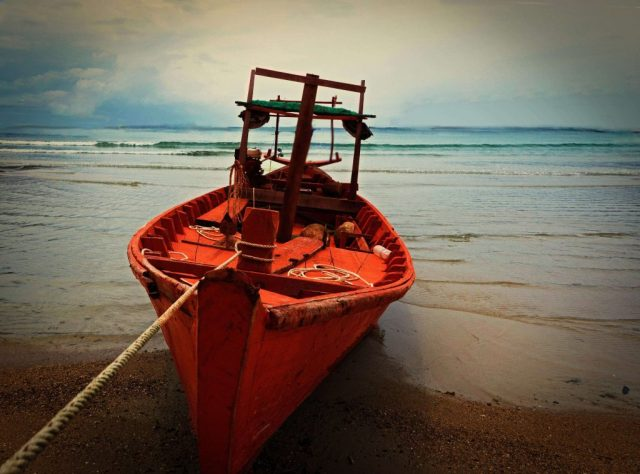 Red-boat-on-shore-Cambodia-travel-photography-gallery