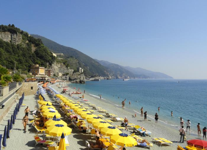 Gele parasollen en een kalme zee aan het strand van Monterosso al Mare