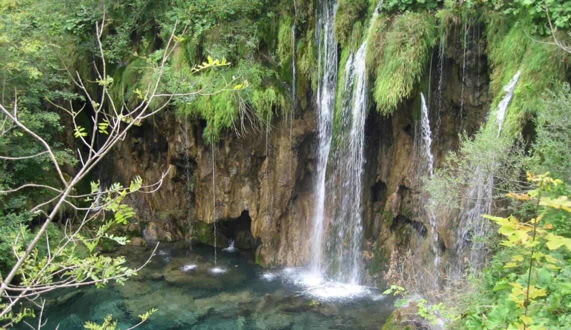 Metershoge waterval klatert te midden van veel groen naar beneden