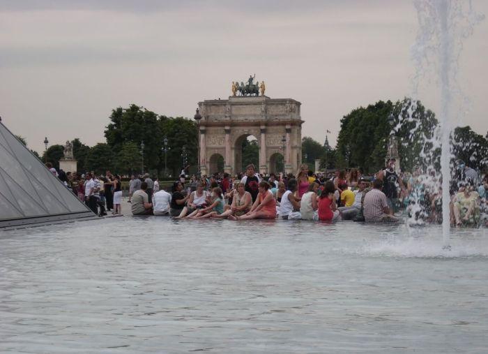 Pootje badende mensen bij het Louvre met de Arc de Triomphe du Carrousel op het achtergrond