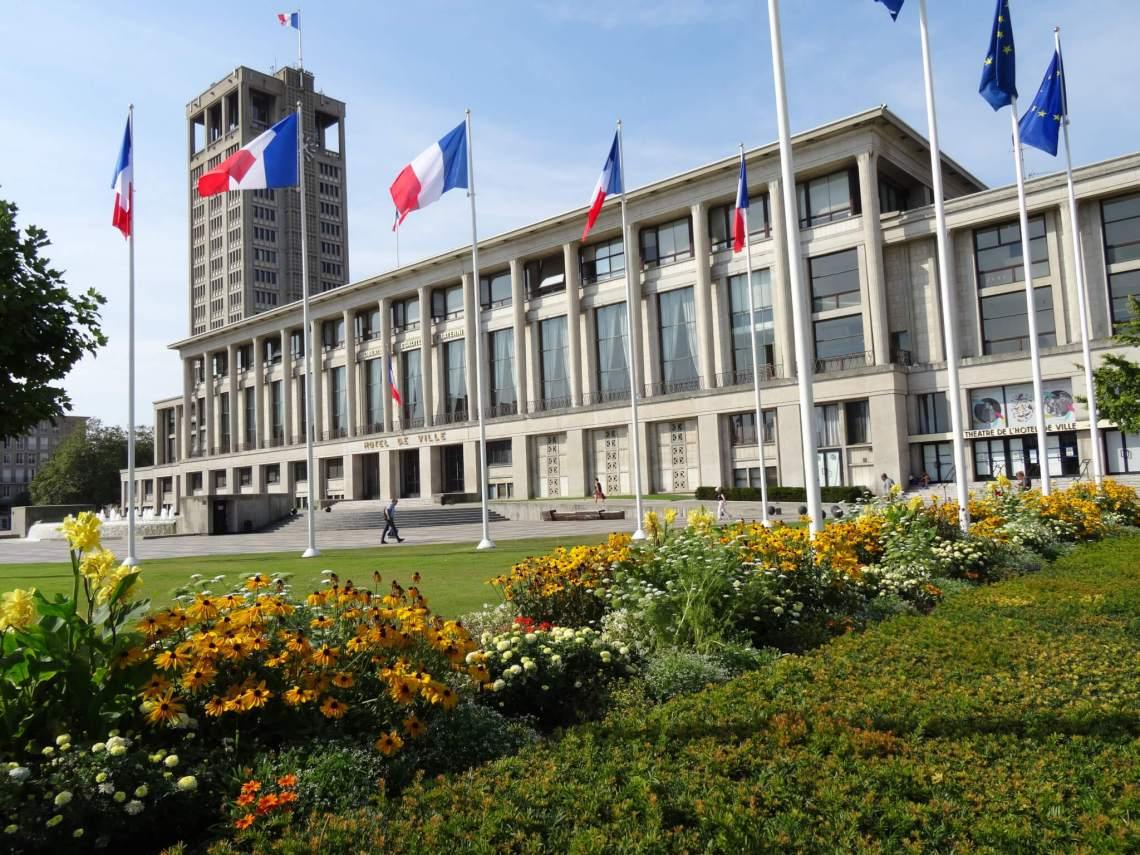 stadhuis van Le Havre met op de voorgrond Franse vlaggen en bloemen
