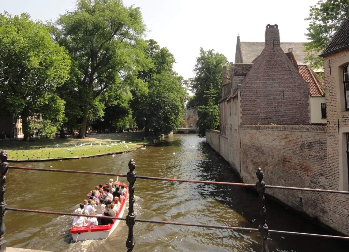 Toeristenboot vaart voorbij muur van begijnhof Brugge grenzend aan het water