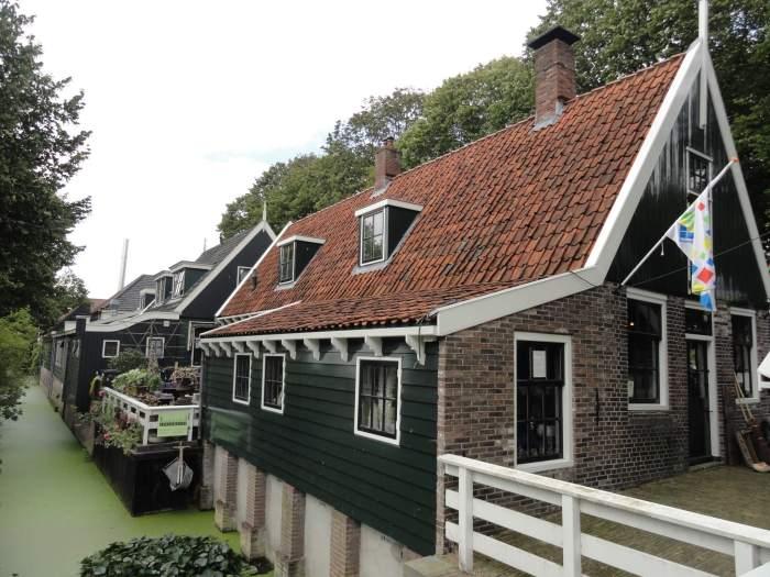 Knusse huisjes aan het water met groene, houten afwerking en rode dakpannen