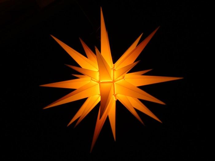 Oranje lichtgevende kerstster in donkere nacht