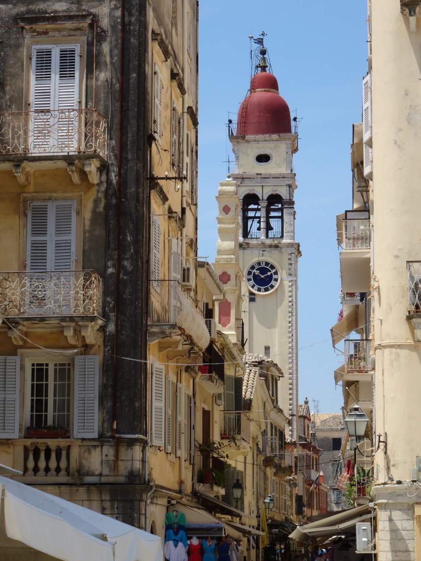 Beige klokketoren te midden van steegje in stadscentrum Corfu