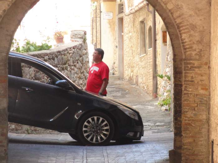 Parkeerproblemen in San Gimignano, een auto staat vast in de nauwe straten