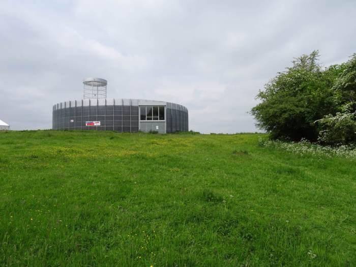 Het ronde bezoekerscentrum in Spiennes op een groene heuvel