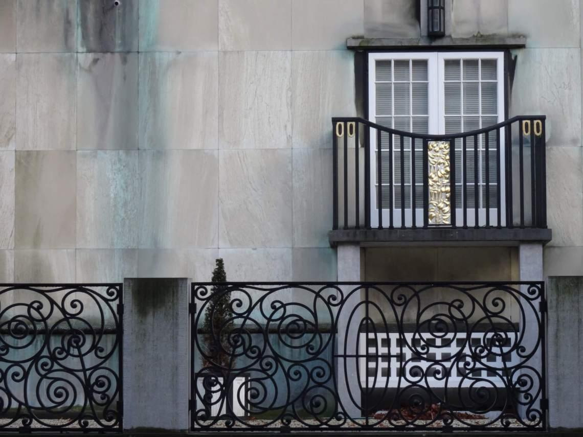 Zwart en goud siersmeedwerk van hek en balkon