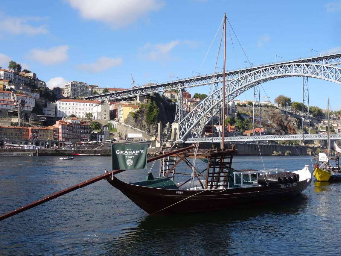 Een oud vrachtschip aan de kade in Porto met brug op de achtergrond