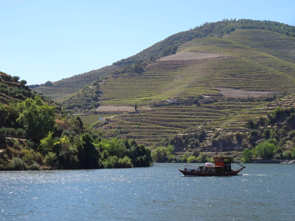 Op de Douro vaart een oud vrachtbootje tussen heuvels vol wijnranken