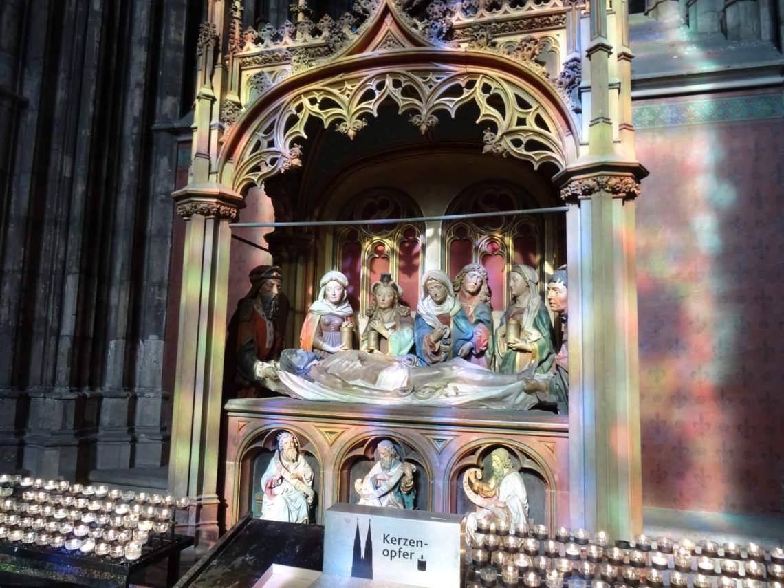 Zonlicht door glas-in-lood ramen geeft aparte kleurschakering op beeldhouwwerk van groep rouwenden rondom dode Jezus