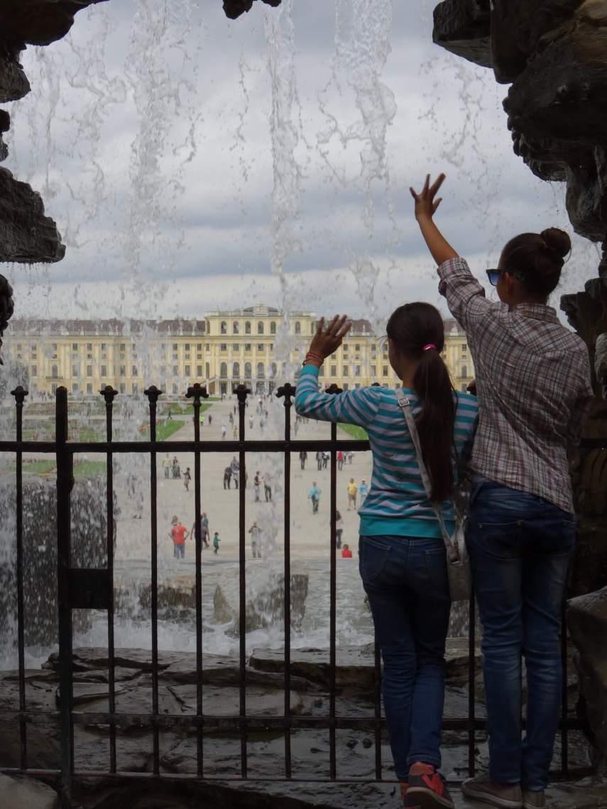 Twee zwaaiende meisjes bij een fontein in de tuin van paleis Schönbrunn