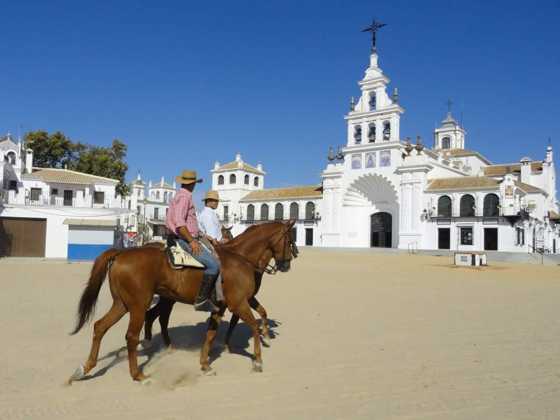 Twee cowboys te paard passeren witte kerk in cowboydorp El Rocio