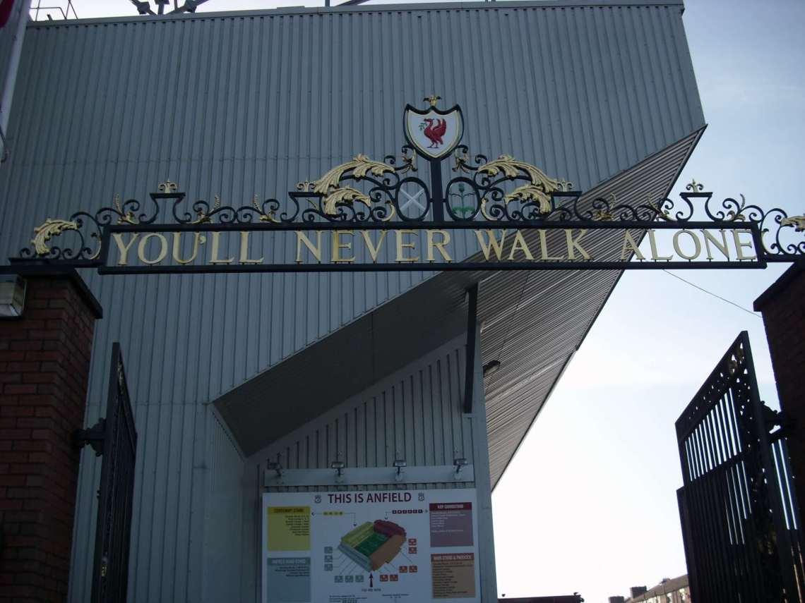 De tekst You'll never walk alone op een gietijzeren hekwerk voor het stadion van Liverpool