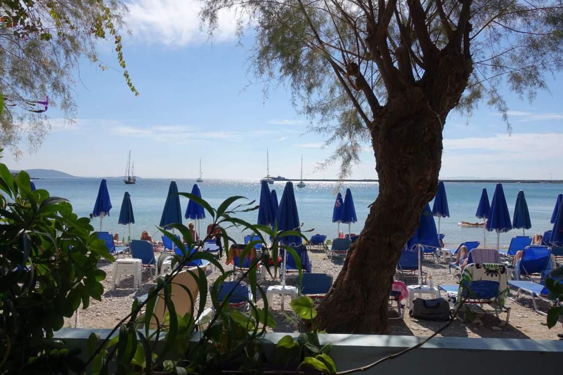 Haven van Samos met blauwe parasollen en een pier op de achtergrond