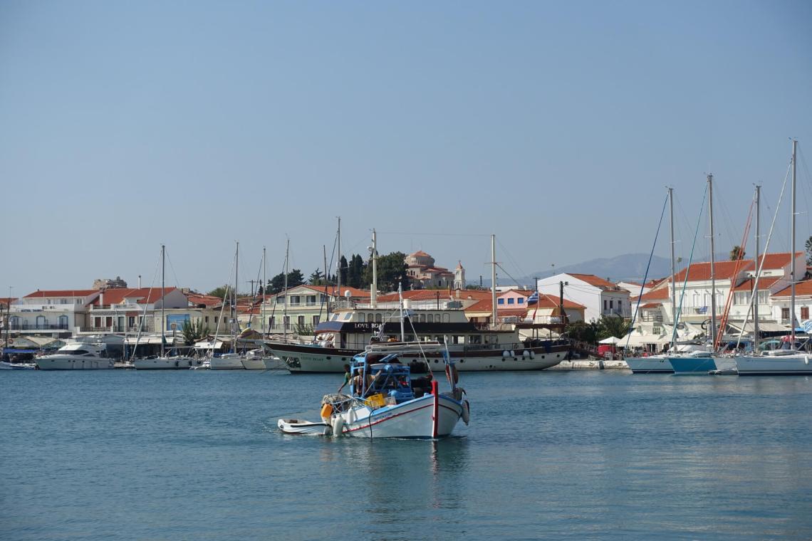 vissersbootje vaart langs kust met zeilschepen en vakantiehuizen