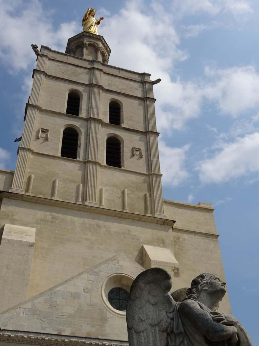 Vrome engel onder de toren van de kathedraal kijkt vol toewijding omhoog