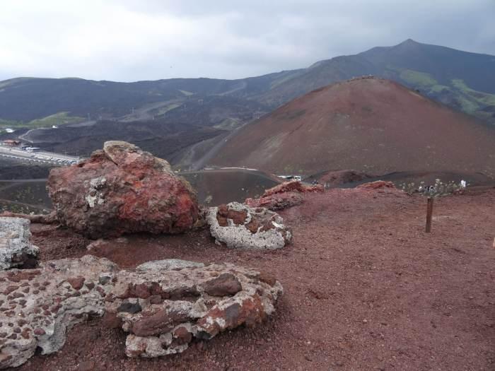 Zicht op parkeerplaats Etna te midden van roodbruine lavastenen en heuvels