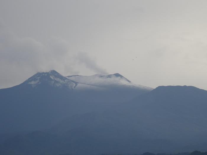 Besneeuwde top van Etna vulkaan met rookpluimen