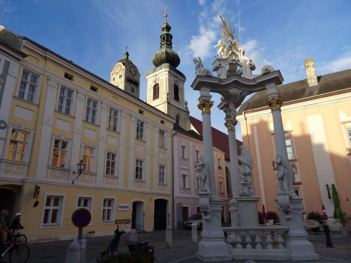 Drie zuilen en barokke kerk in Krems