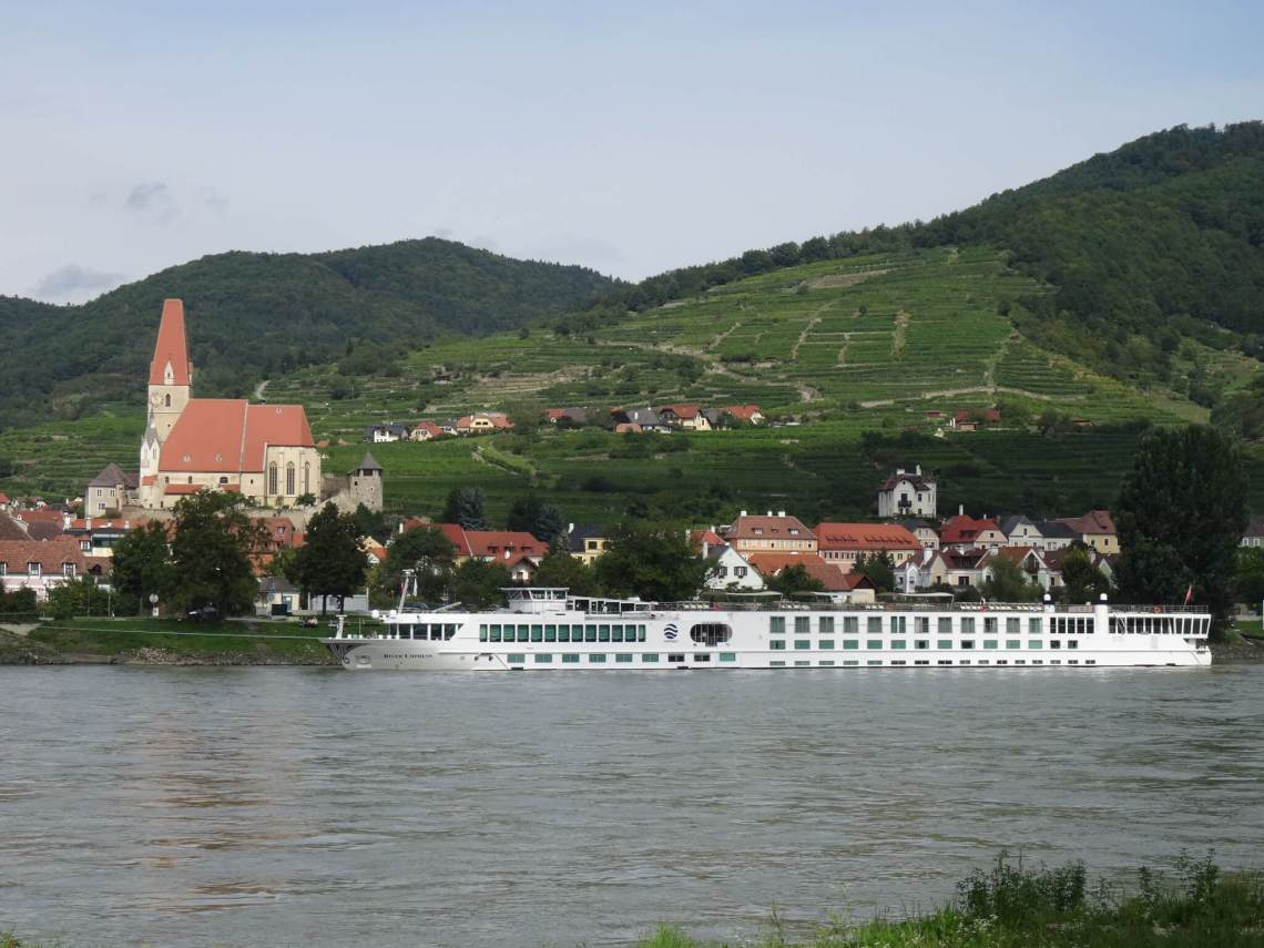 Met zijn hoge witte kerk, groene wijnterrassen en blauwe Donau is Weissenkirchen de Wachau in een notendop