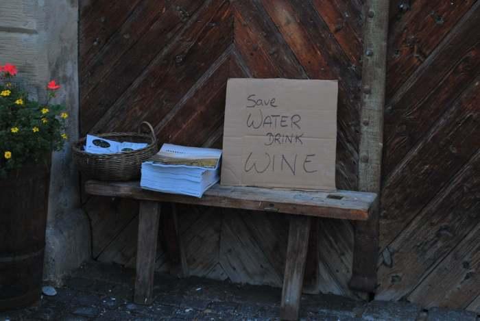 """Op een stuk karton staat geschreven """"save water, drink wine"""""""