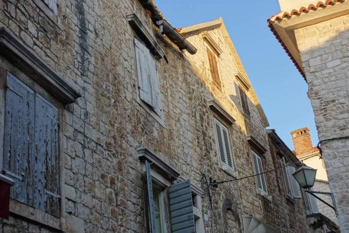 Gevels in Trogir met patina en afgebladderde verf op raamluiken