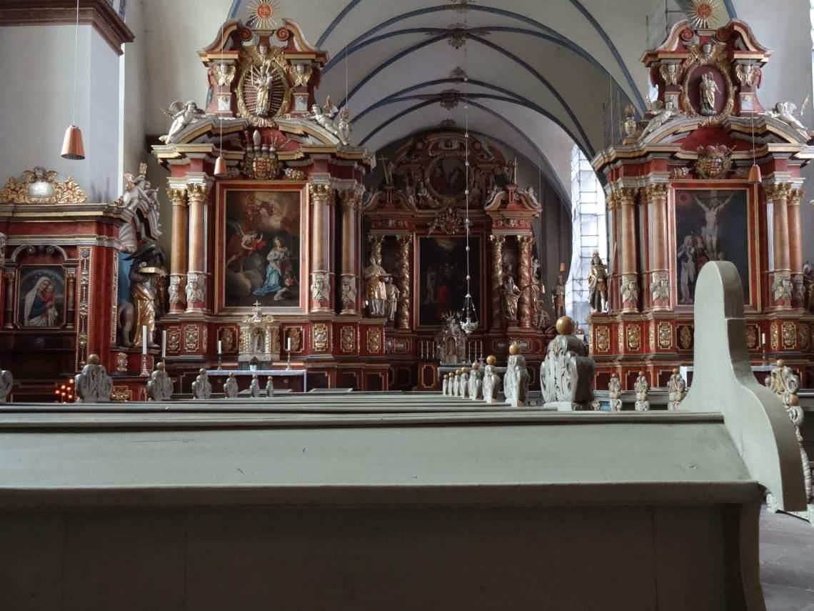Barok interieur van kloosterkerk met veel rood en goud