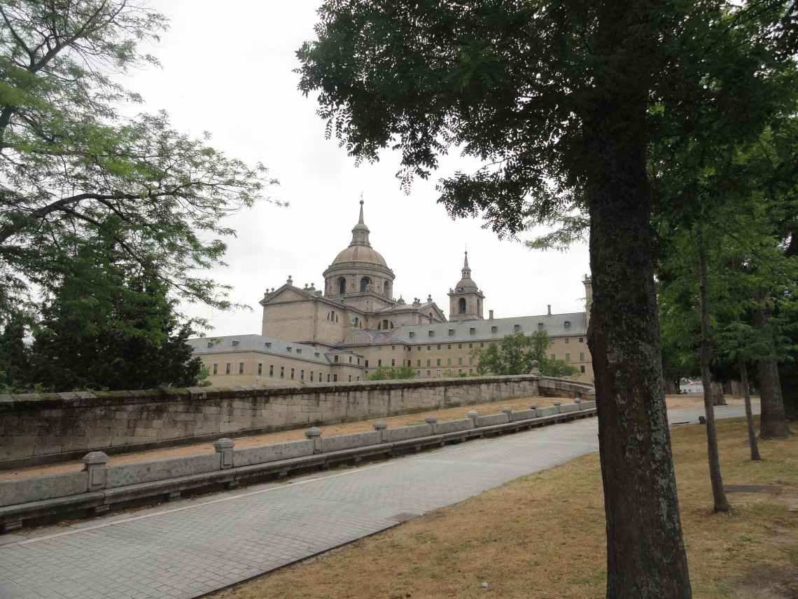 Grijs pad omzoomd door bomen leidt naar het Escoriaal met zijn kerktorens