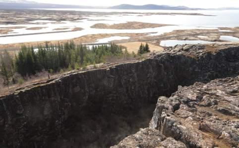 Brede kloof in rotsen met meer op de achtergrond