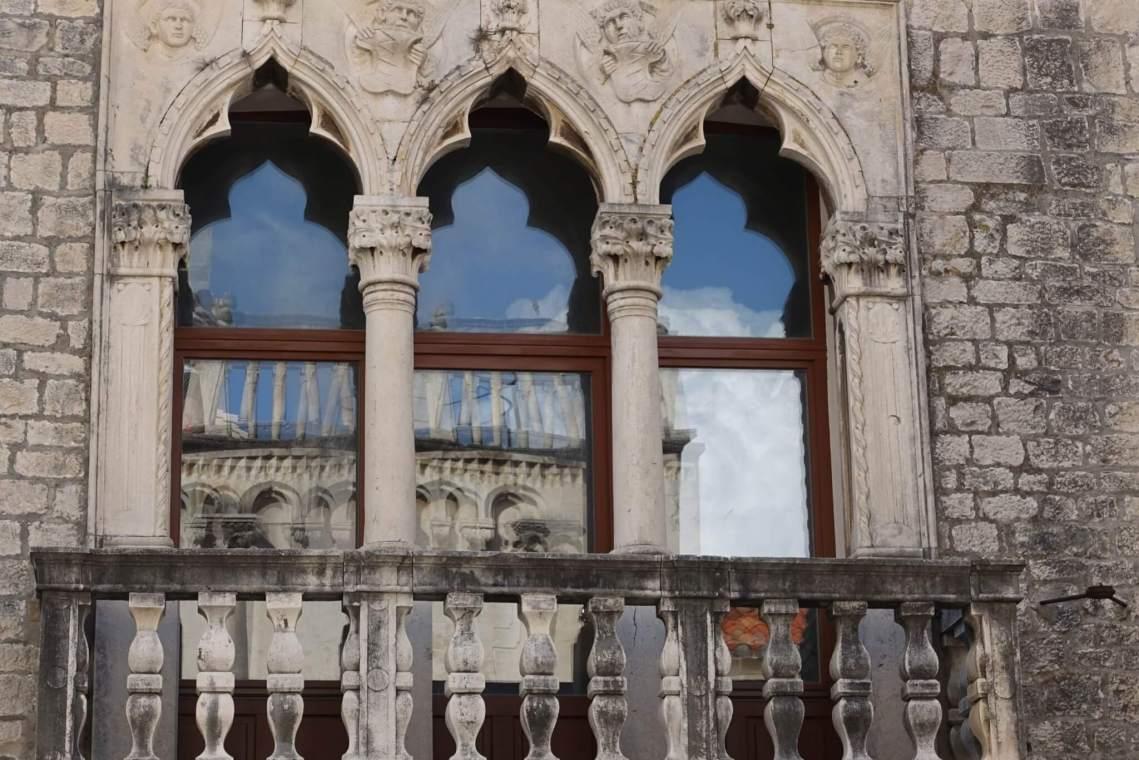Balkon Cipikopaleis met drie door zuilen gescheiden raampartijen